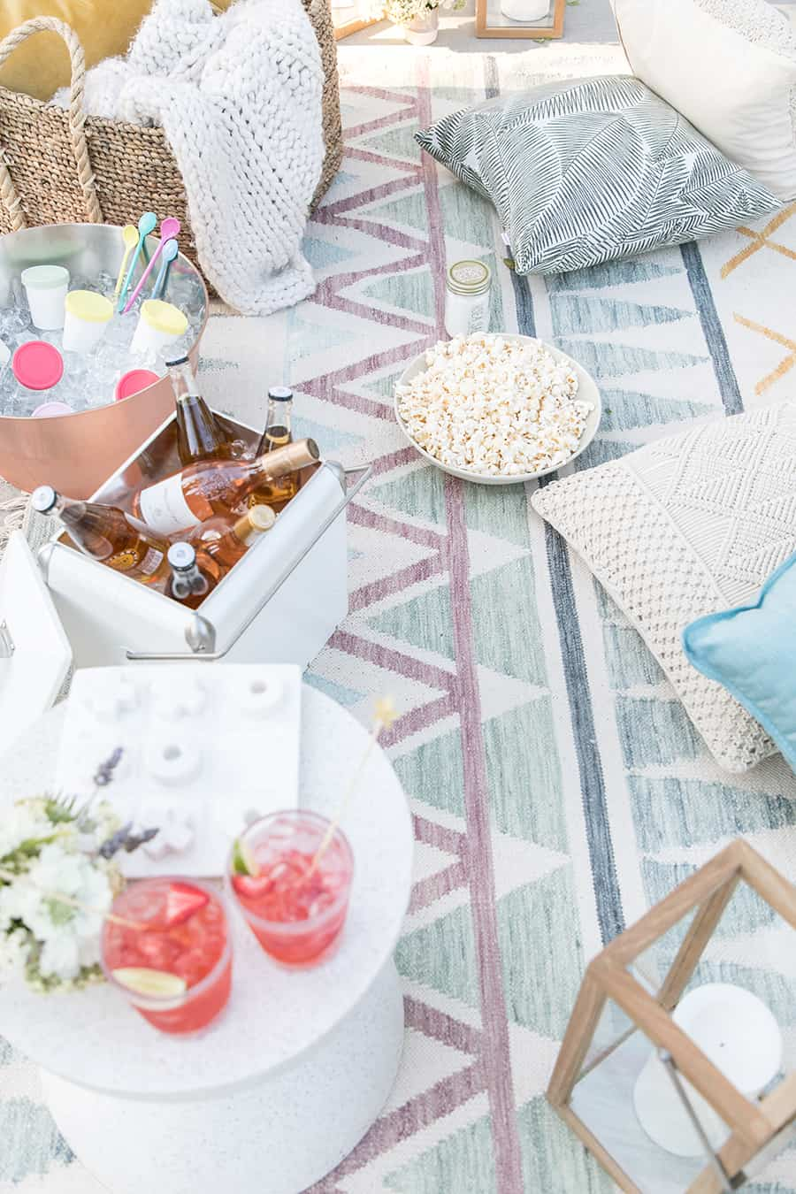 Outdoor movie night with pillows and popcorn, table with cocktails and rose in coolers.