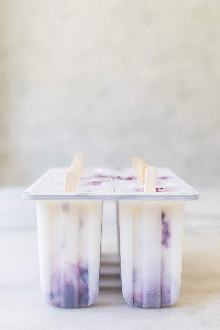 Blueberry popsicles in a popsicle mold on a marble table.