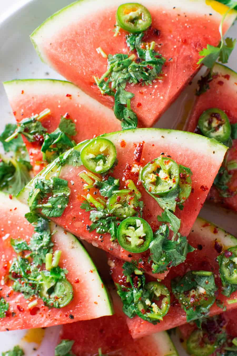 Slices of watermelon with jalapeño and cilantro.
