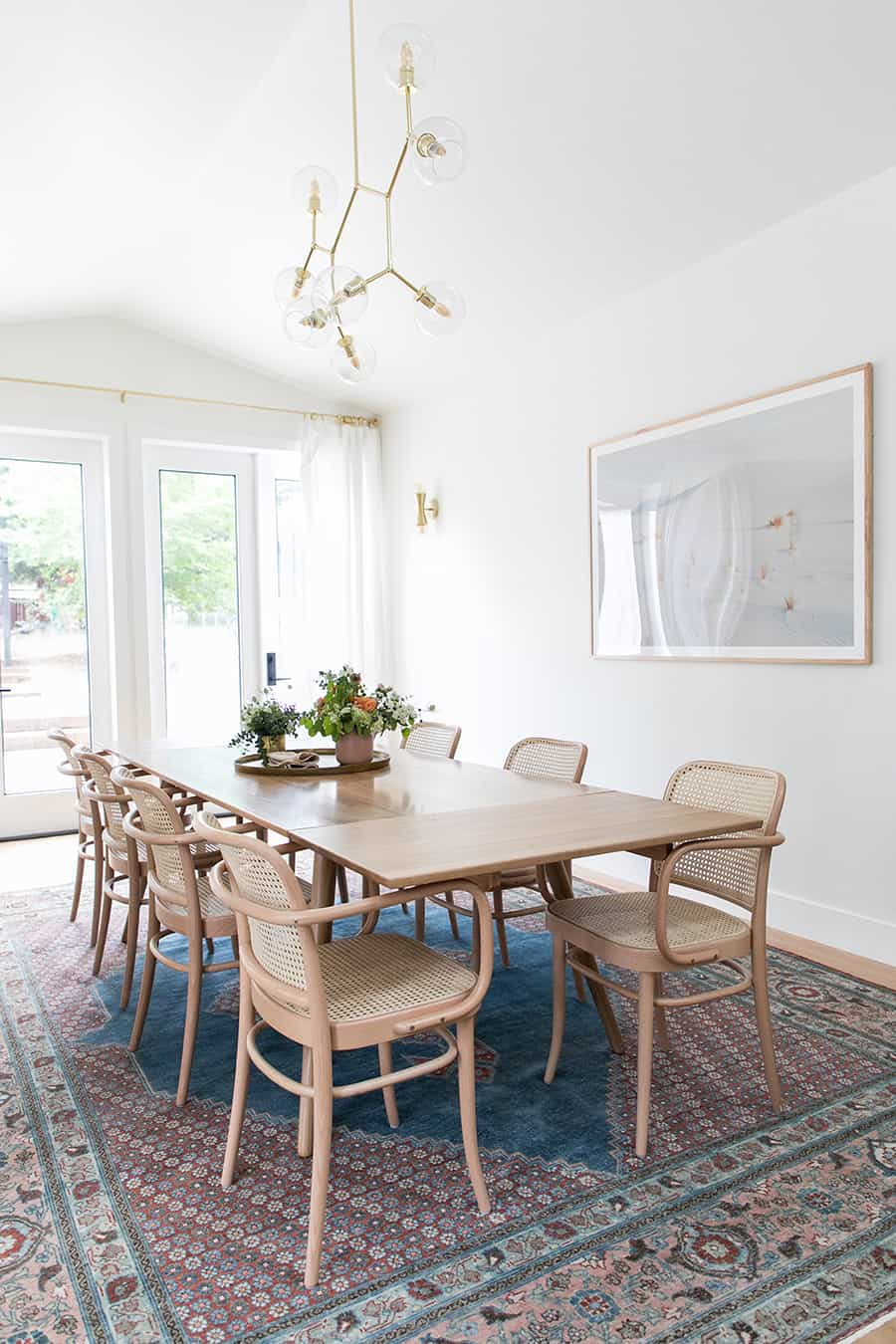 Dining room with blue rug, long table and white curtains