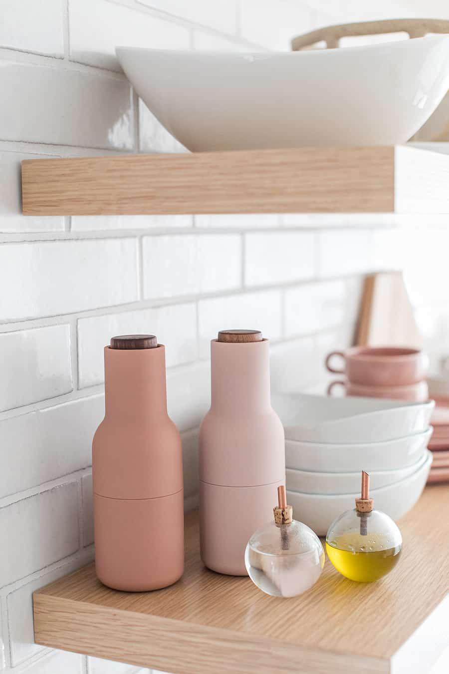 Pink salt and pepper grinders.