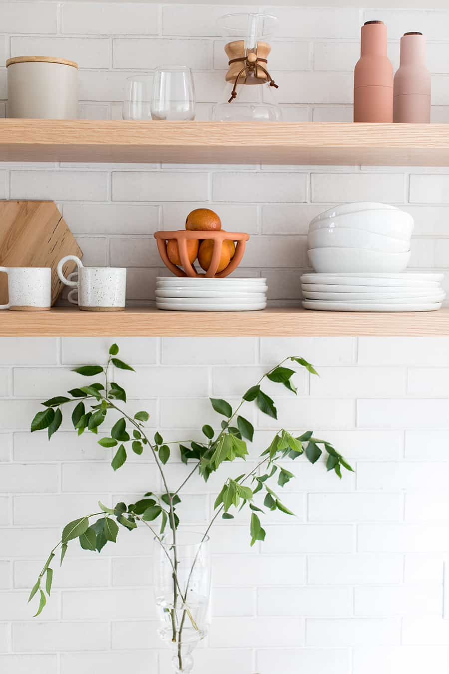 Long wooden open shelving with white plates and white tile.