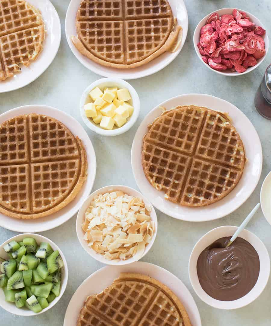 Belgian overnight waffles on pink plates with toppings.