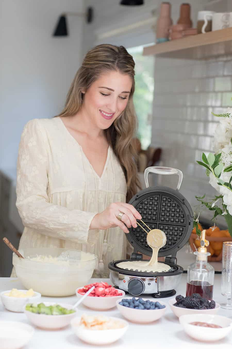 Eden Passante pouring batter into a round waffle maker.