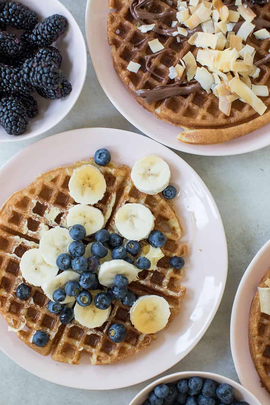 Homemade waffle with bananas, blueberries and syrup.