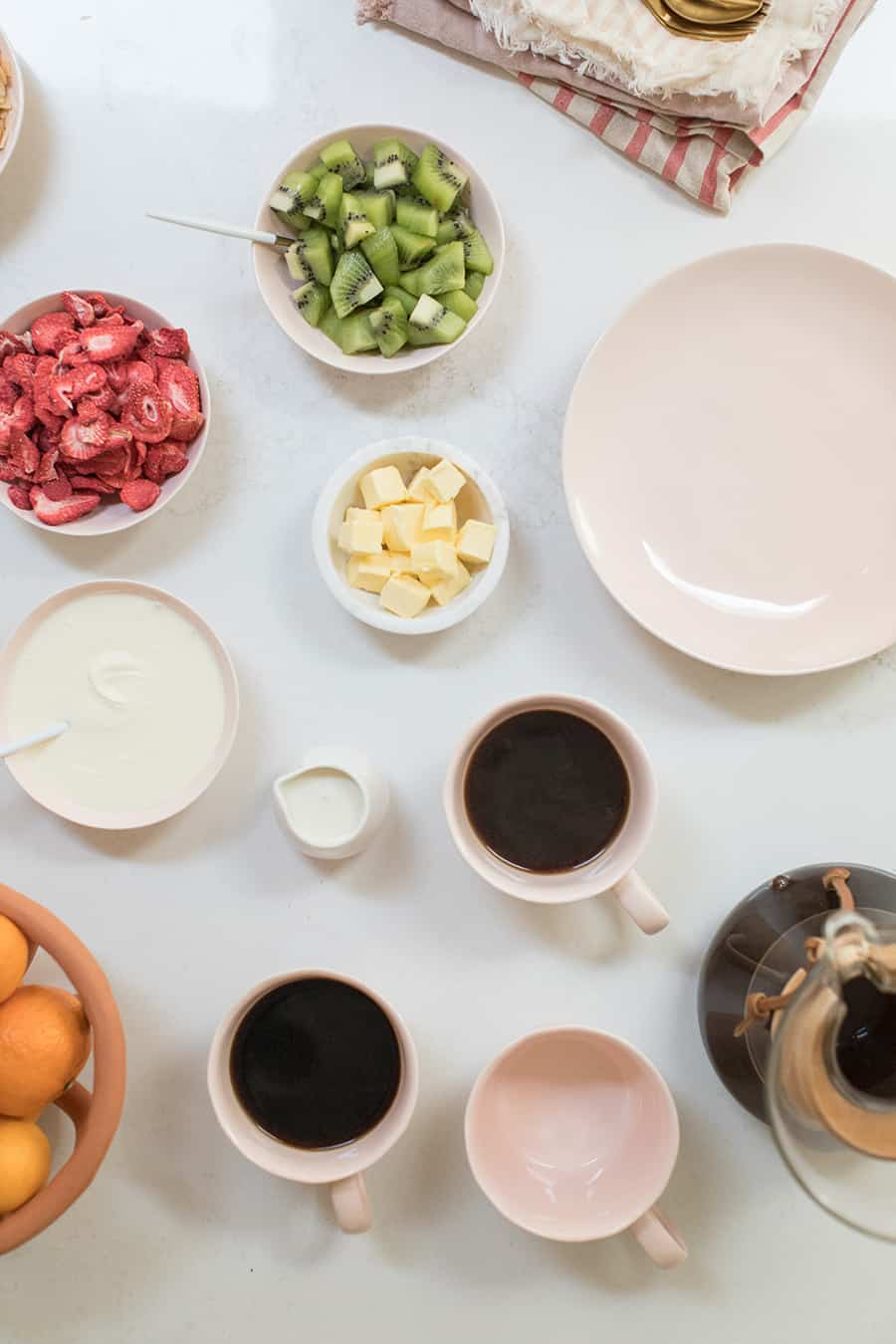 Pink dishes, coffee, butter, oranges and cream on a marble counter.