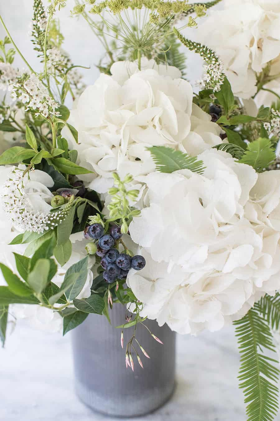 White and green flowers with blueberries in a galvanized vase.