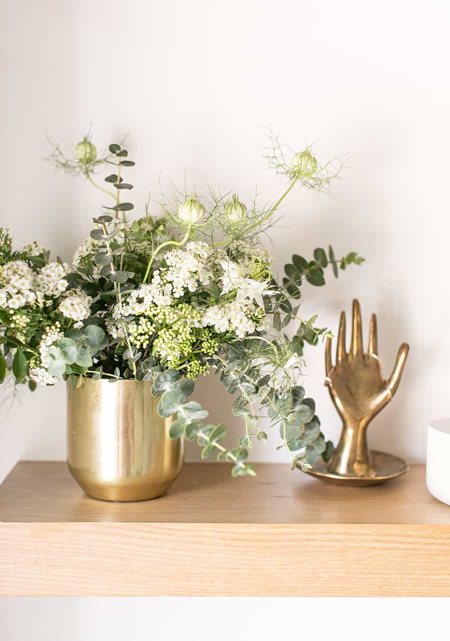 Gold vase with flowers and a gold hand with rings.