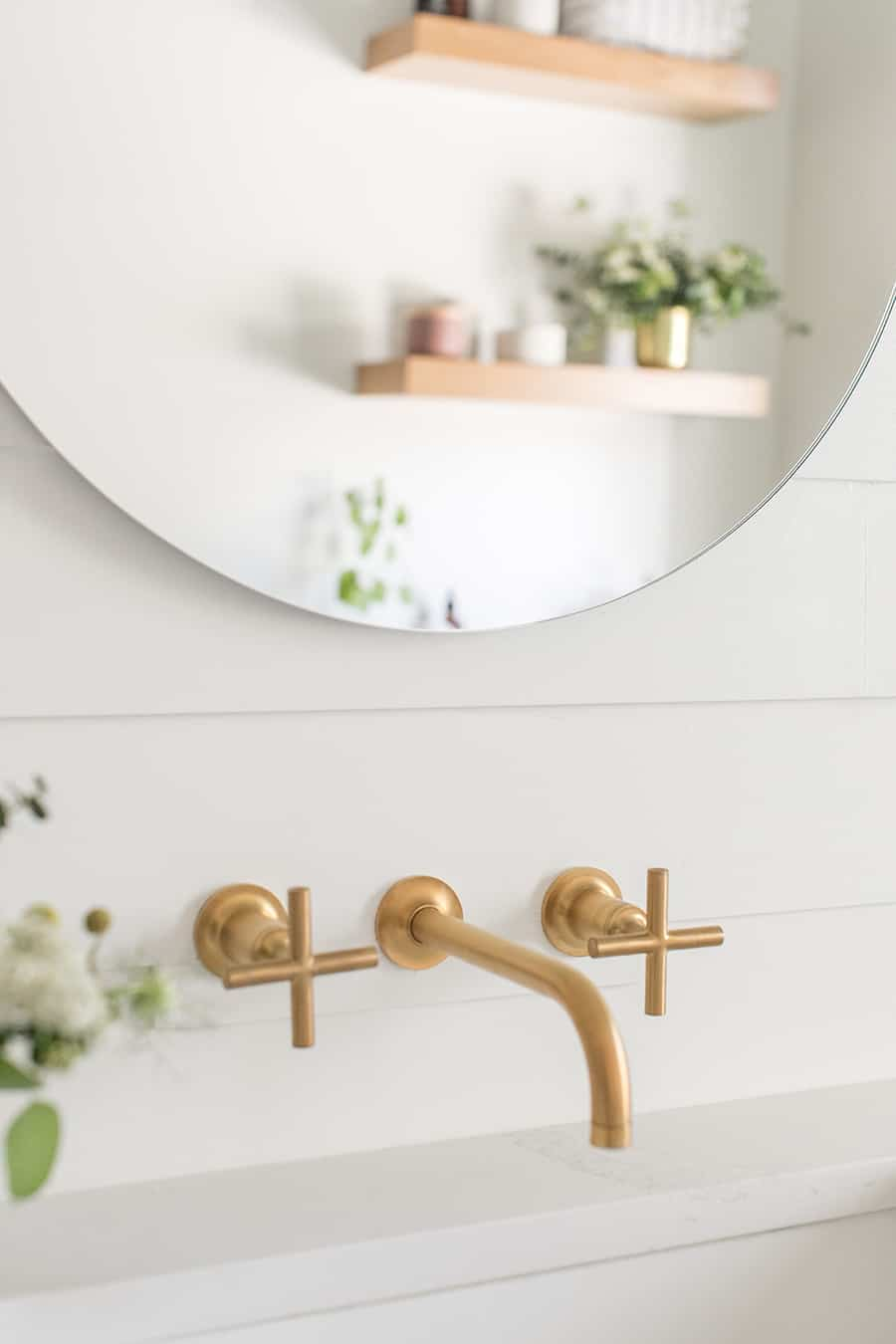 Gold Kohler bathroom faucet with round mirror.