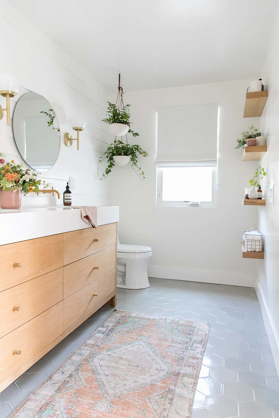 Bathroom with fireclay tile, custom vanity, hanging plants, flowers and built in shelving.