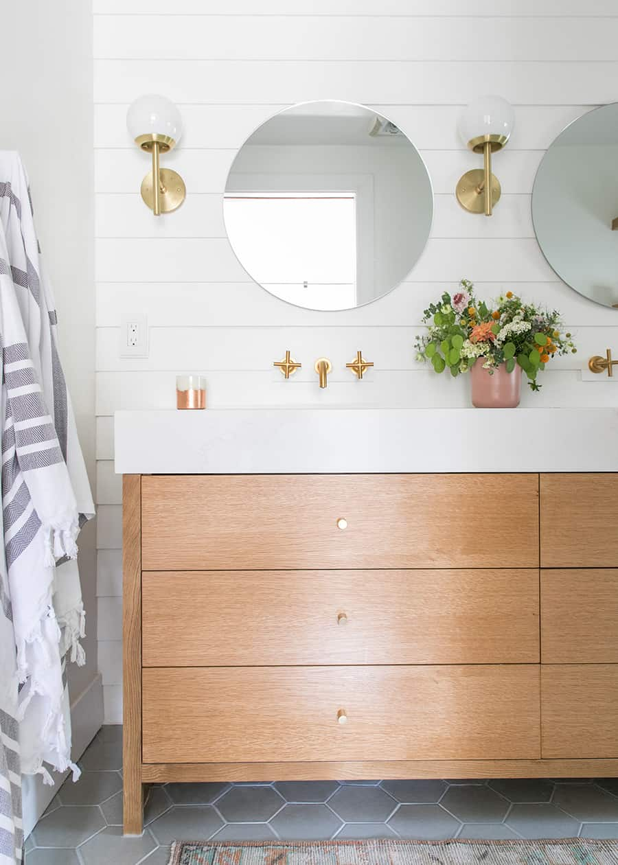 Custom bathroom vanity with three drawers, round mirror, gold hardware, gold scones.