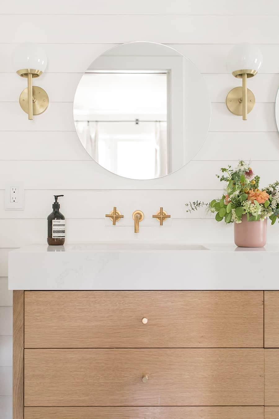 Charming bathroom vanity with thick counter top and three drawers, round mirror and flowers.