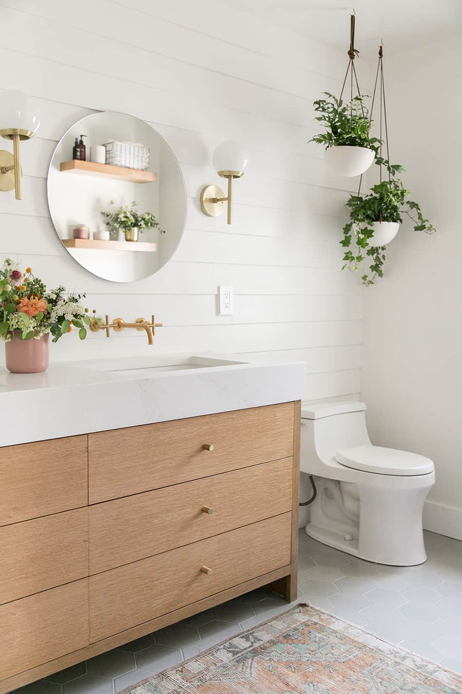 Modern, charming bathroom with hanging plants and wooden vanity.