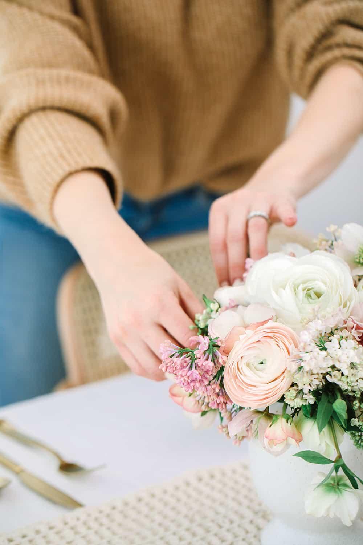 Hands making a floral arrangement.