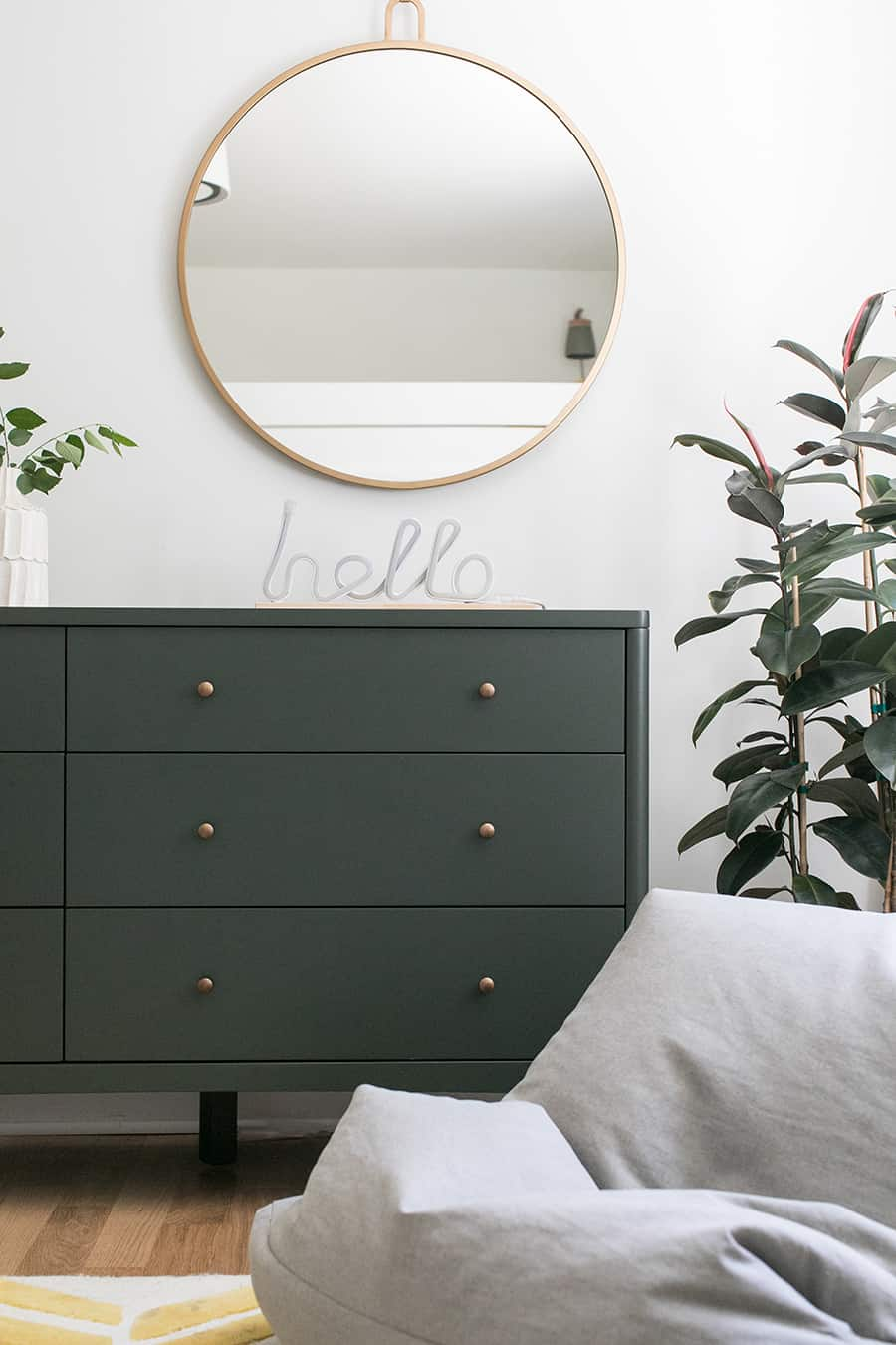 Olive green dresser with hello sign and a gold mirror