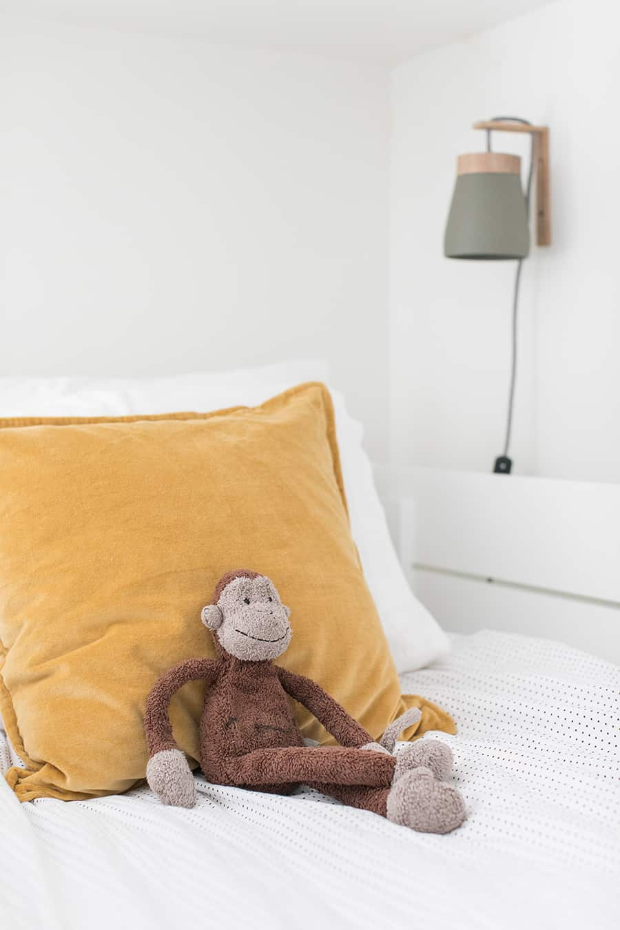 Kids bedroom with velvet yellow pillows and a stuffed monkey.