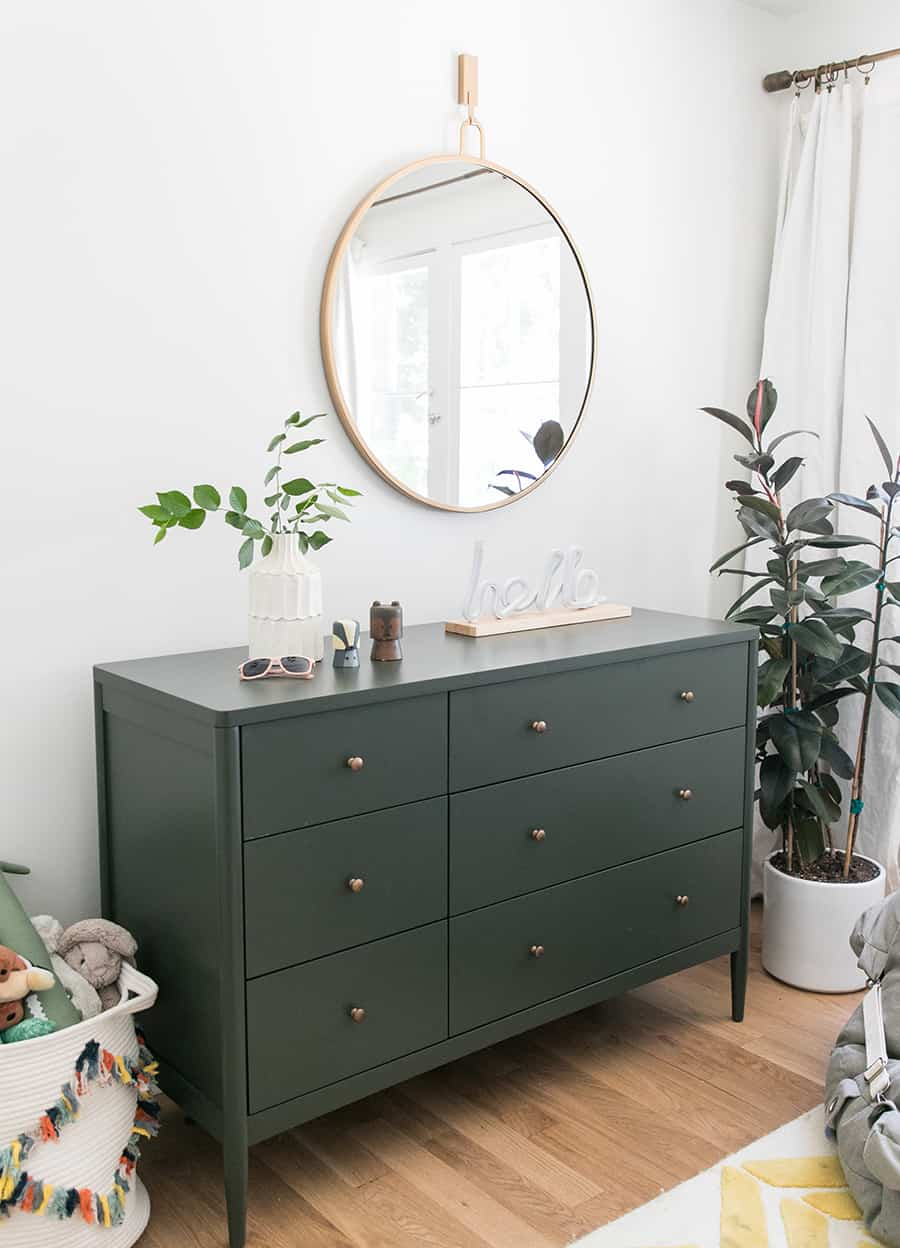 Olive green dresser with plant and a gold mirror.