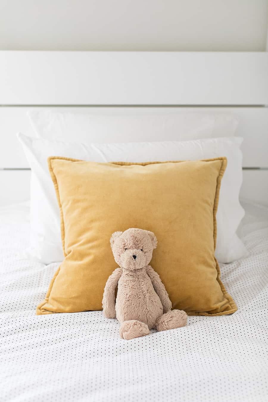 Velvet pillows with a stuffed teddy bear.