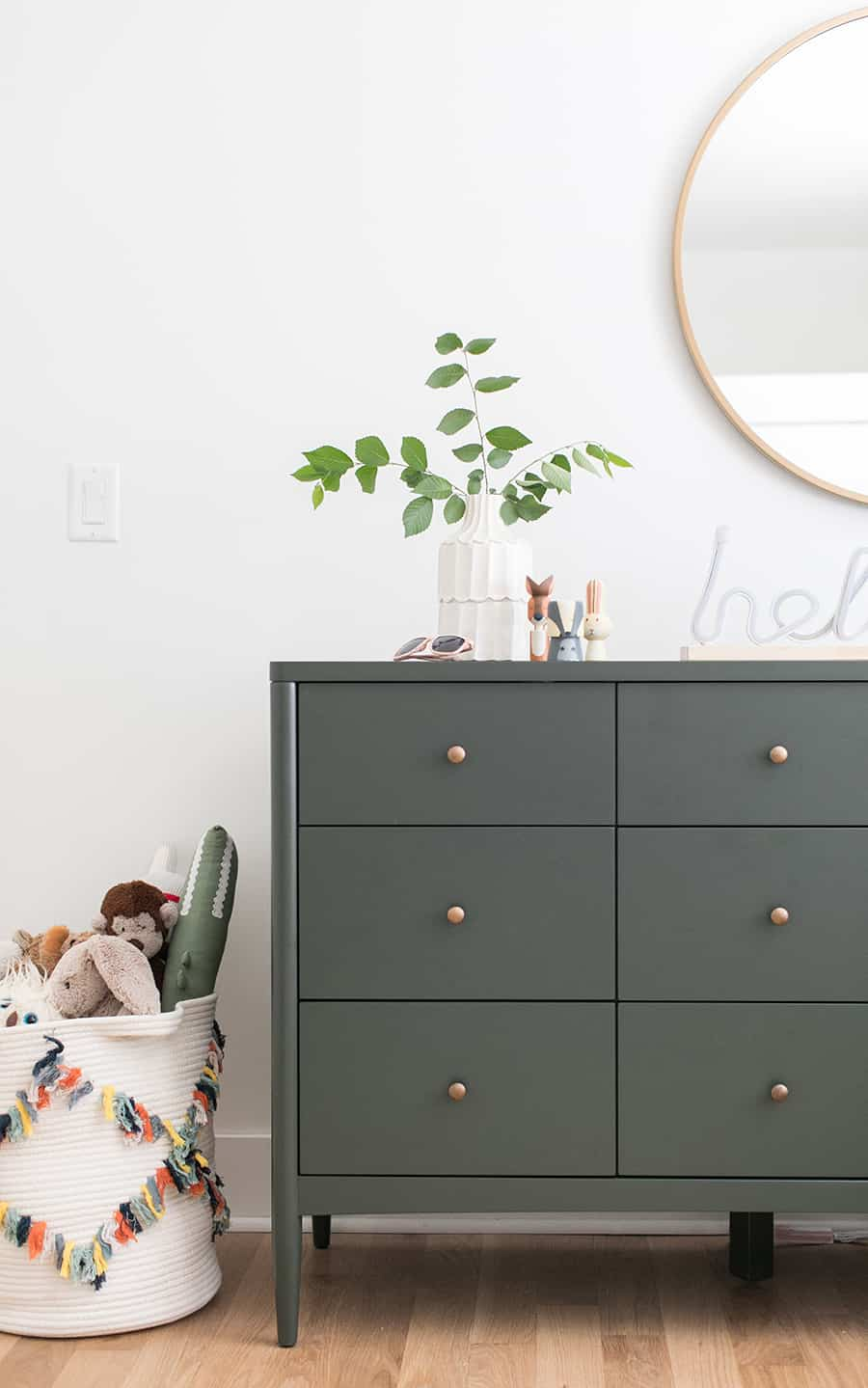 Boys room with an olive green dresser and a gold mirror.