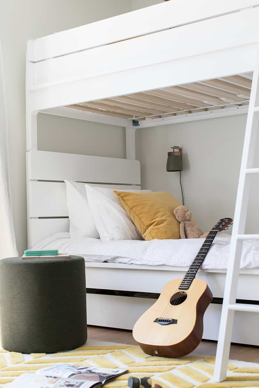 White bunkbeds in a boys room with yellow pillow, white bedding and a guitar.