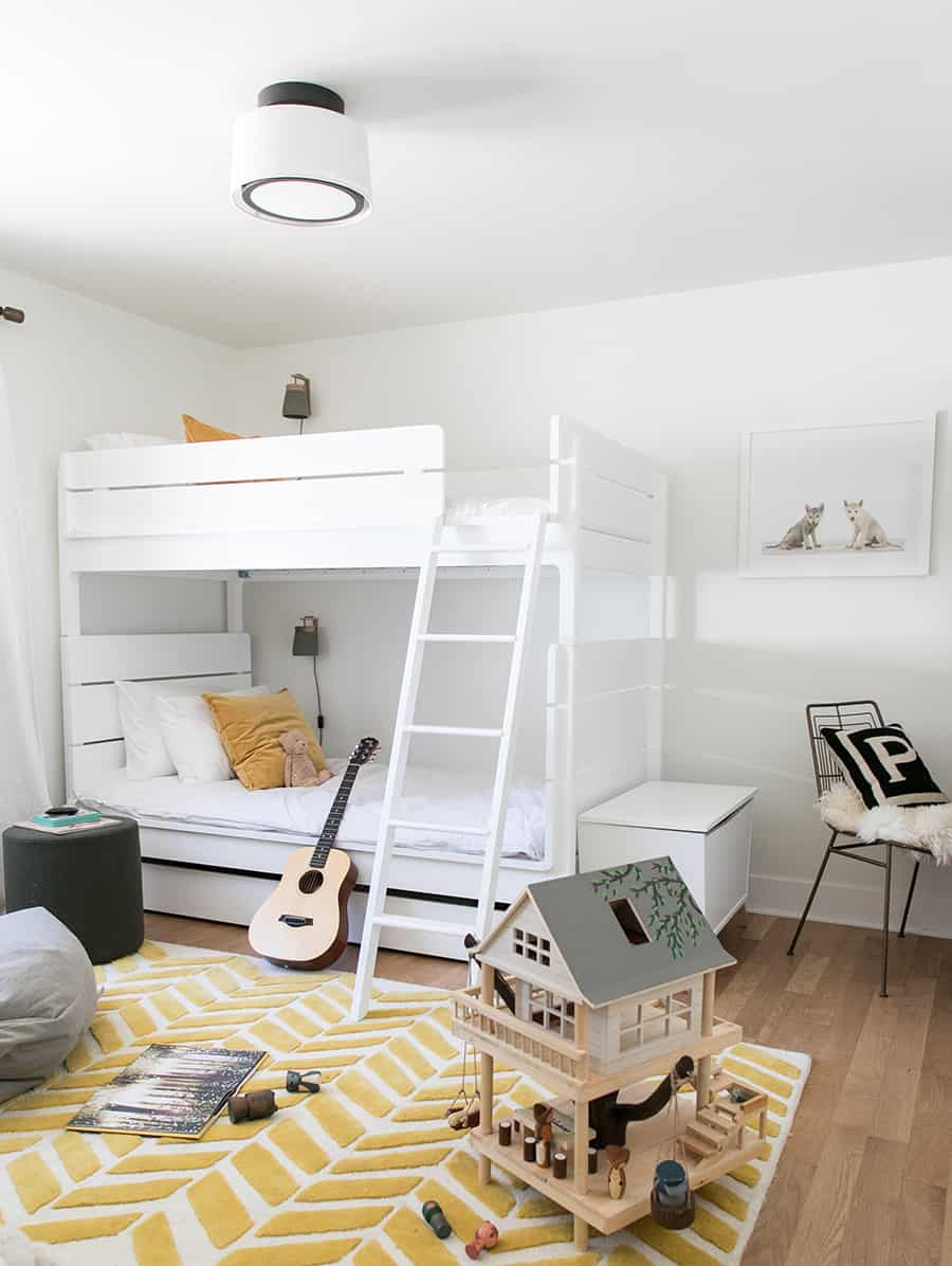 Boys room with white bunkbeds, yellow rug and a tree house toy.