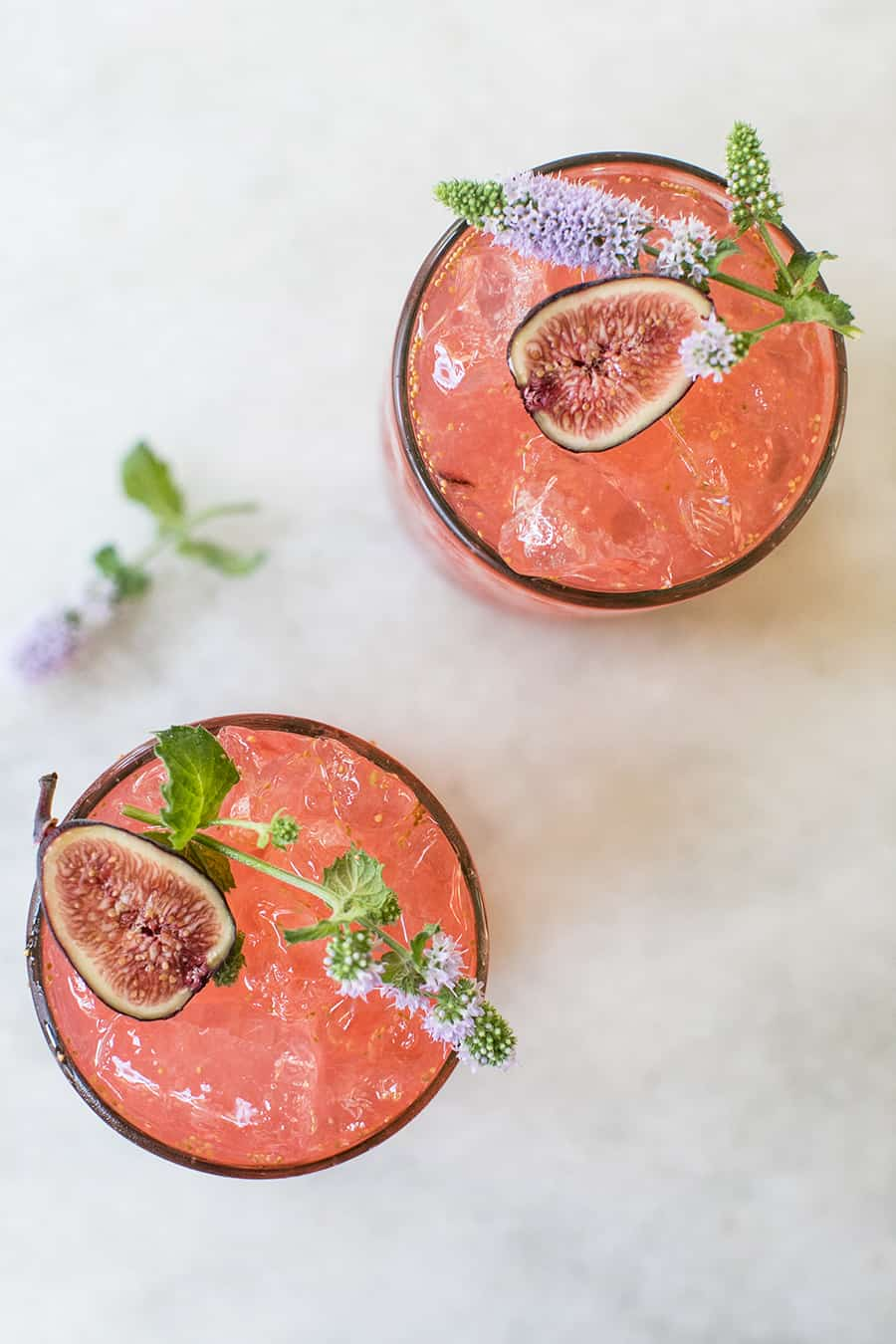 Pink cocktail with figs and edible flowers.
