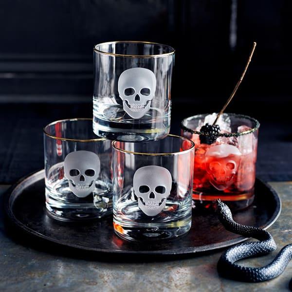 Skull glasses on a black platter with a snake