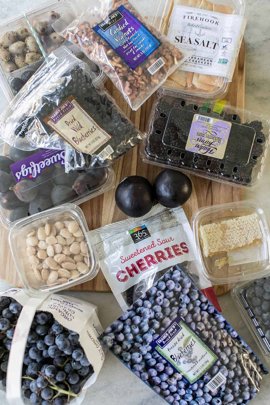 Berries, nuts, honey and grapes for a meat and cheese board.