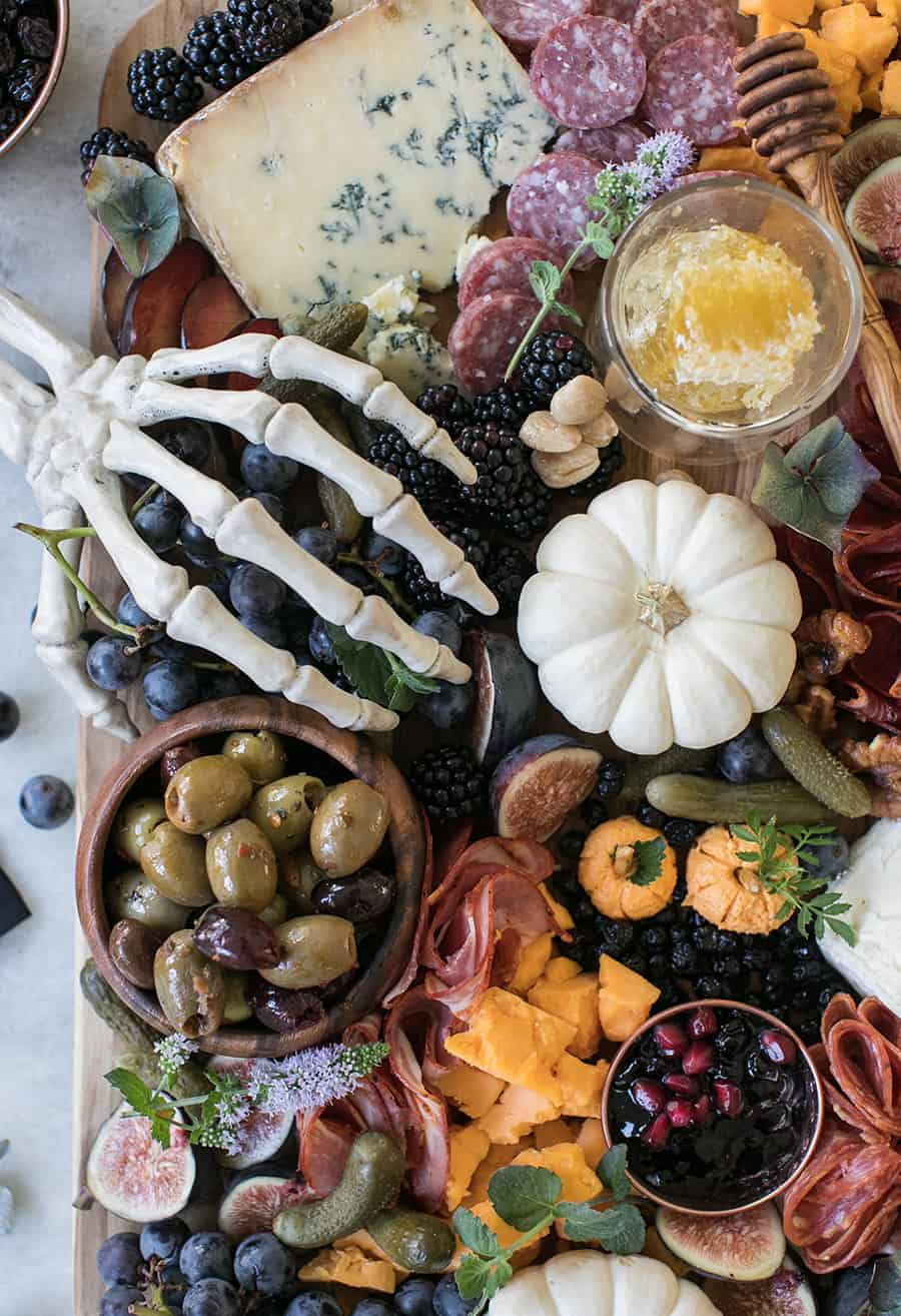 Skeleton hand on a Halloween Meat and Cheese Board with pumpkins, berries, pickles, olives, cheese and meat.