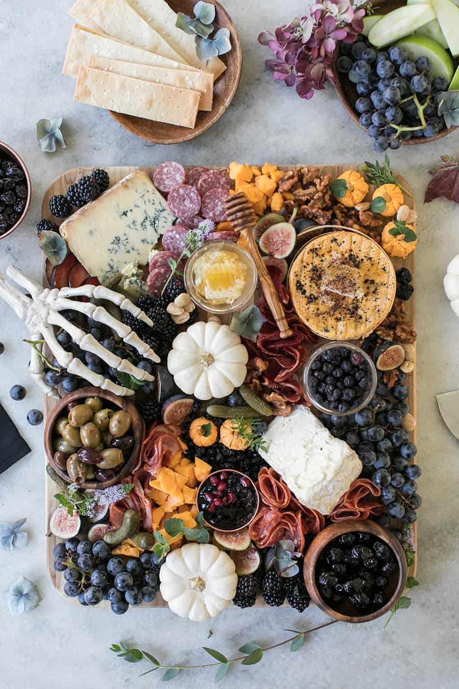 Halloween Meat and Cheese Board with pumpkins, berries, pickles, olives, cheese and meat.