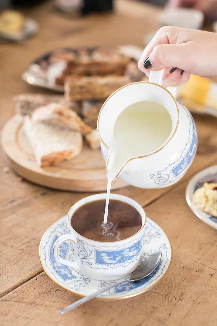 Pouring cream into a tea cup.