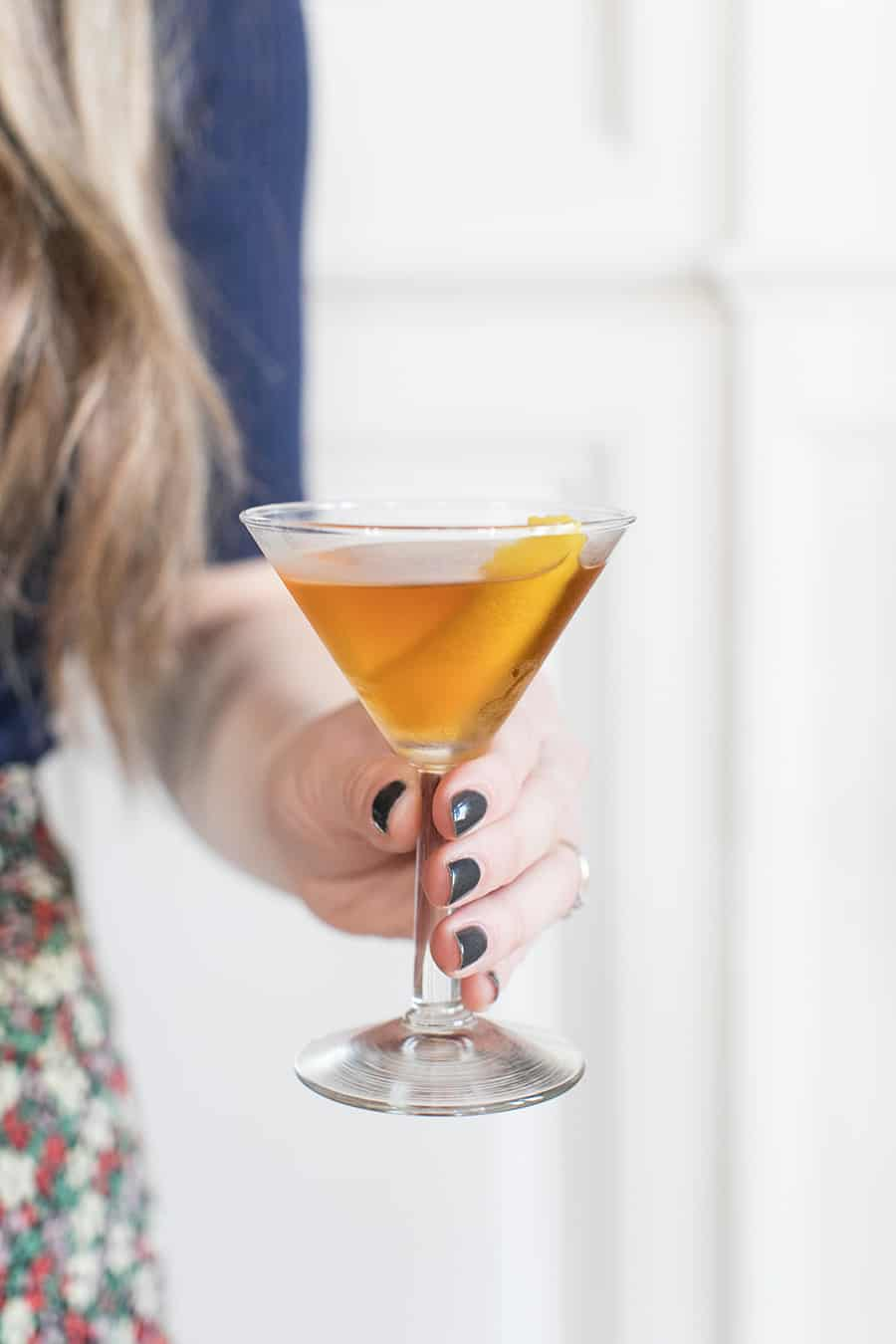 Holding a Bénédictine cocktail in a martini glass.