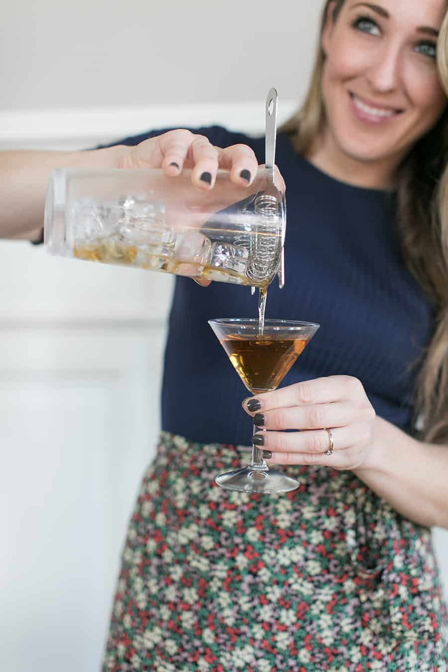 Eden Passante pouring Bénédictine cocktail into a glass.