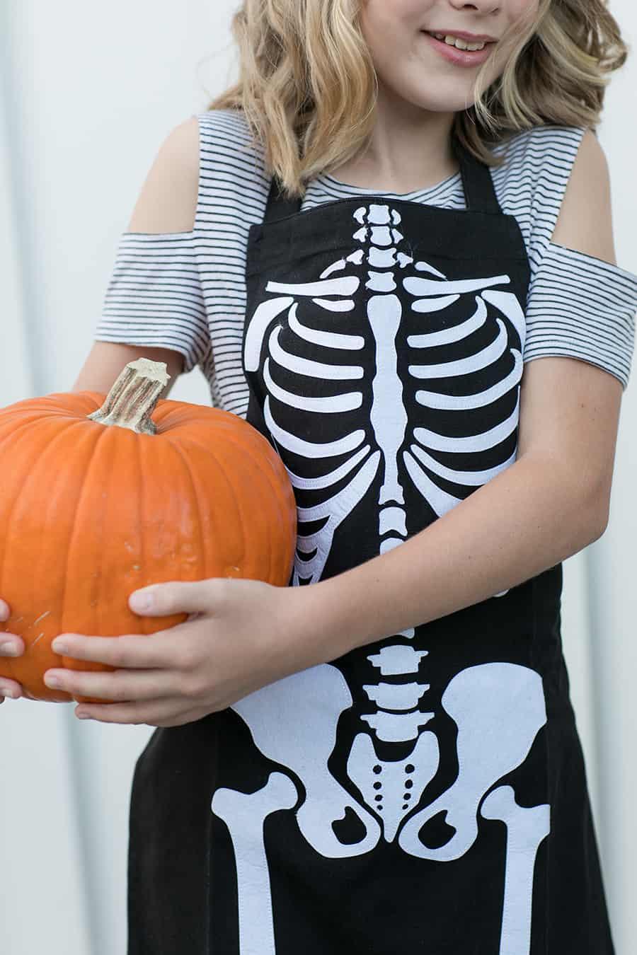 shot of child holding a pumpkin