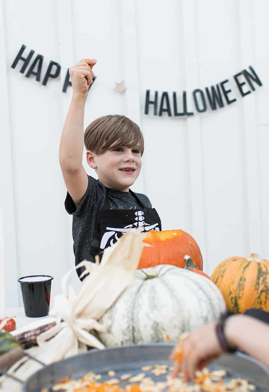shot of child standing behind pumpkins on a table