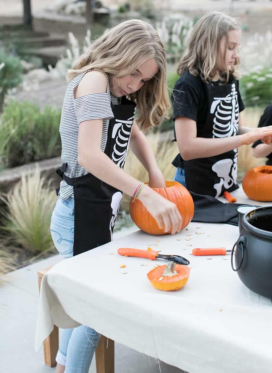 shot of girl carving a pumpkin