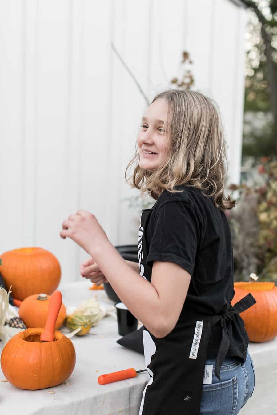 shot of child carving pumpkins