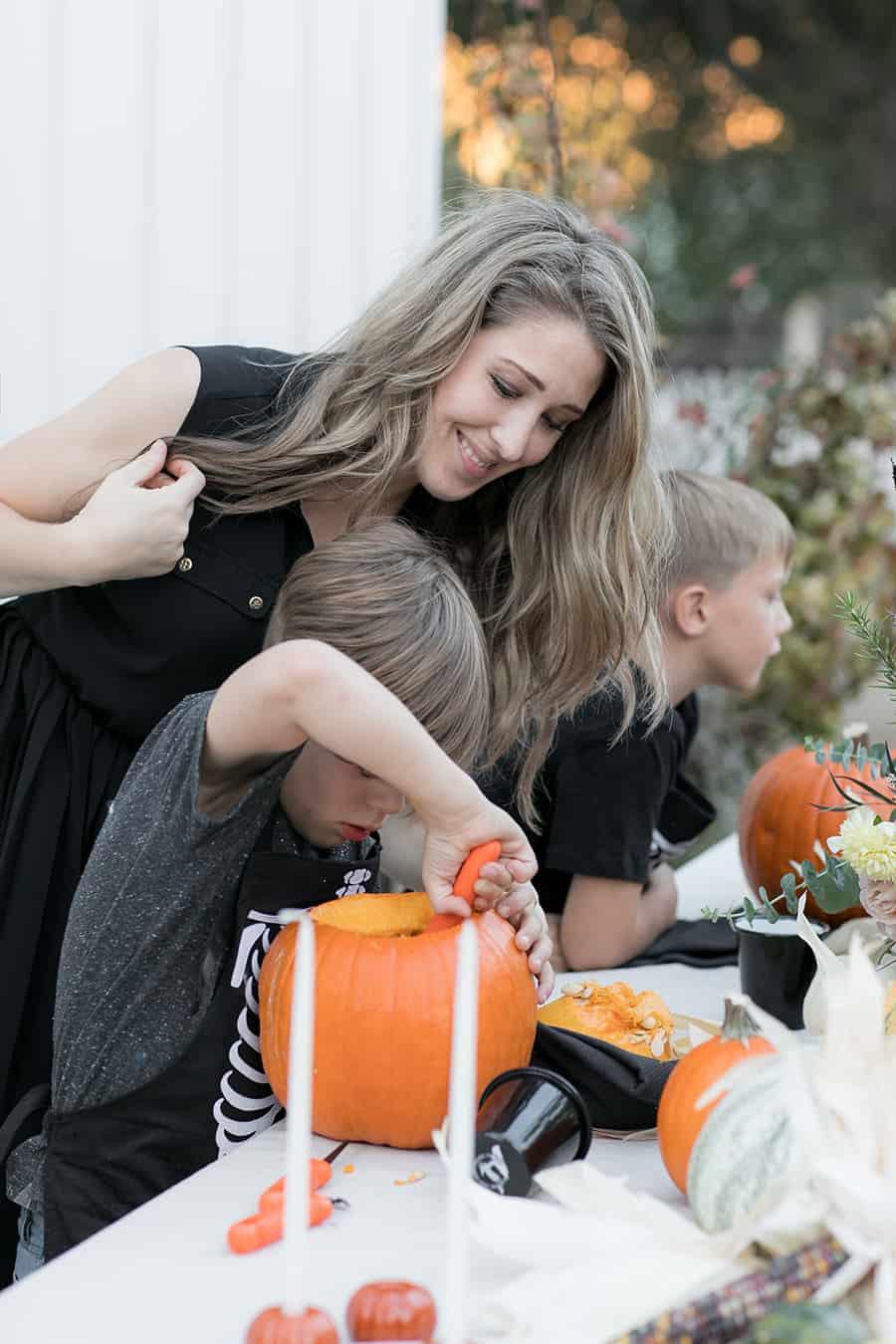 shot of eden helping child carve a pumpkin