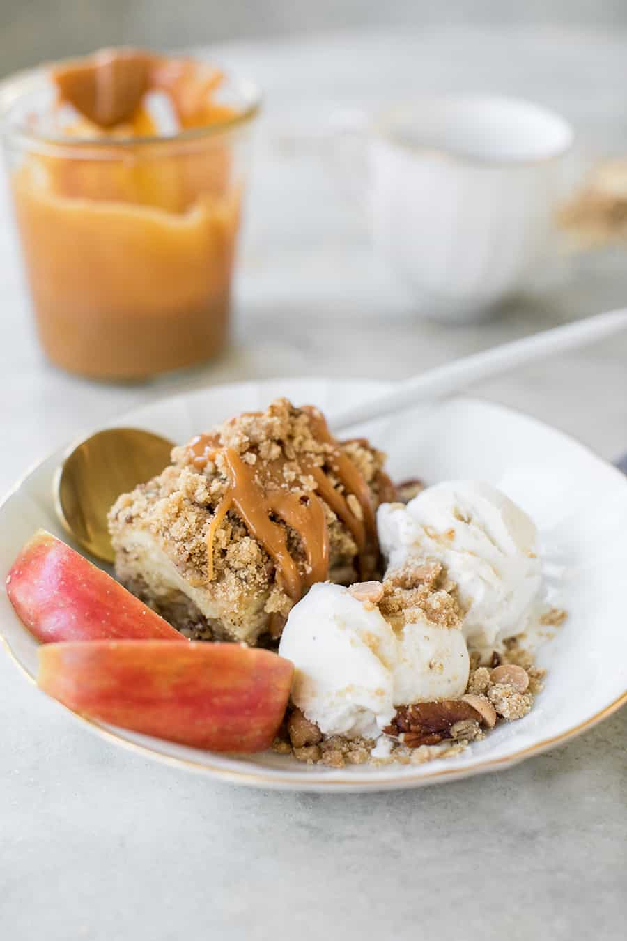 shot of apple crumble bar on a plate with apples and ice cream