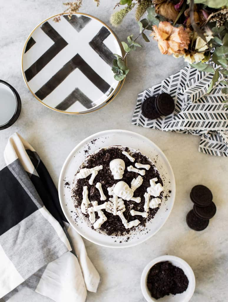 overhead of an Oreo cake with candy skull bones and black and white plates with black and white napkins on a marble table.