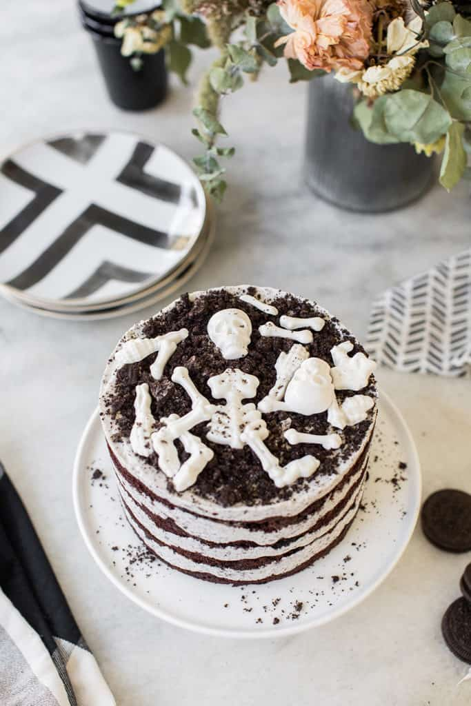 overhead of Oreo cake with white chocolate candy bones on marble table with cake stand.