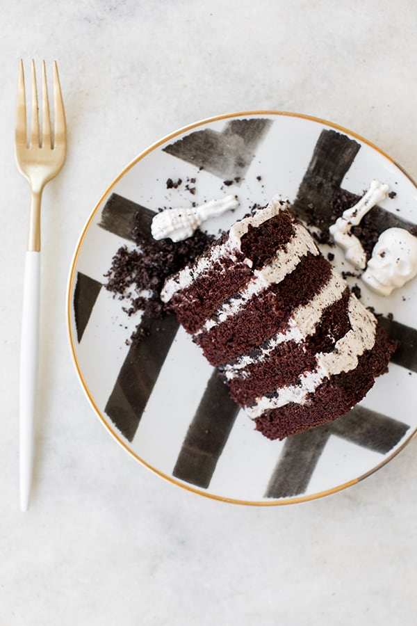Layered chocolate and vanilla cake on a a black and white plate.