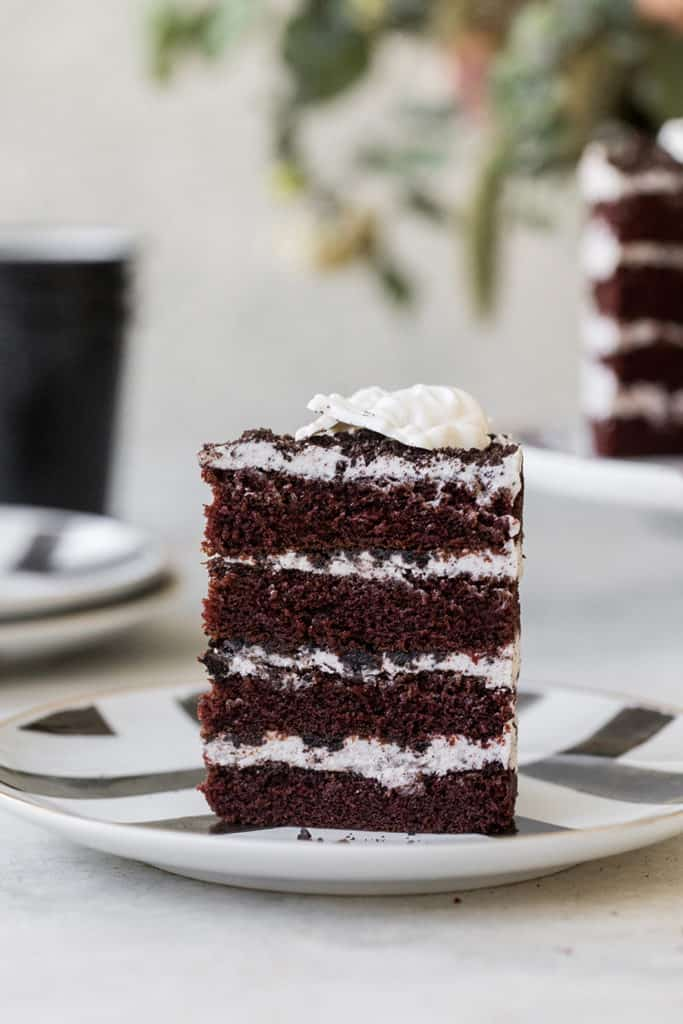 Slice of chocolate cake with layered vanilla frosting standing up on a plate