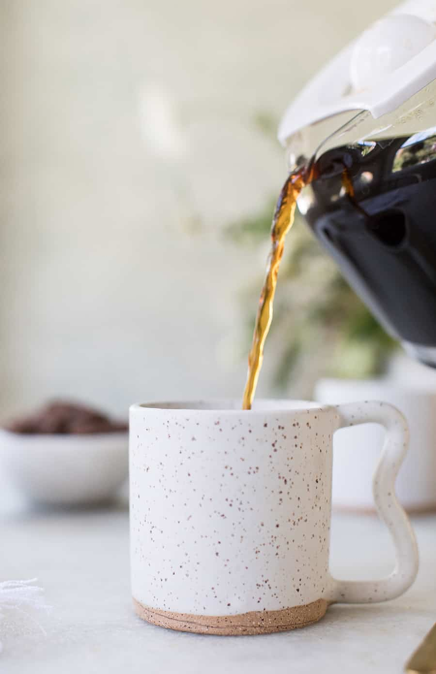 side shot of coffee being poured into a mug