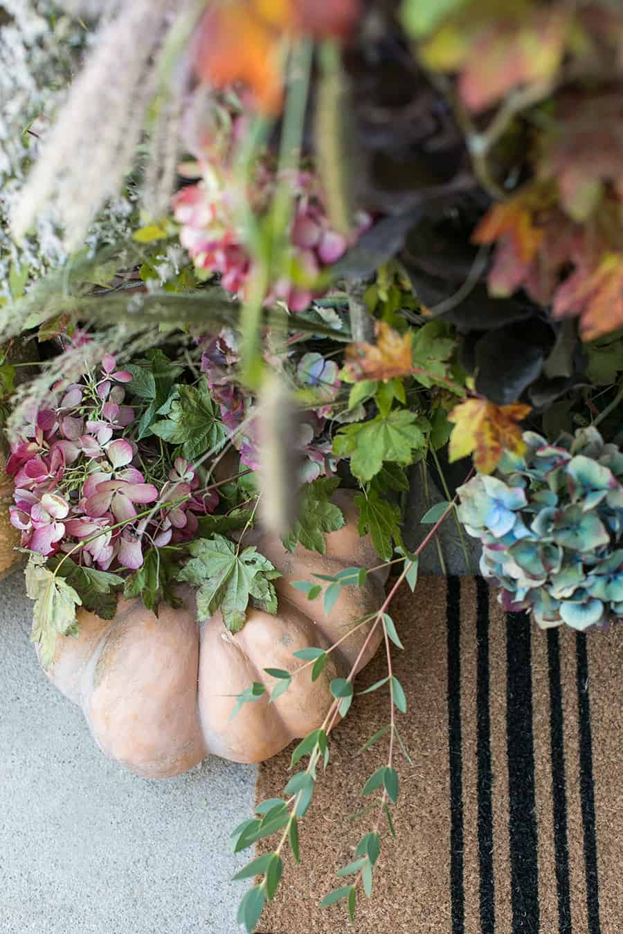 flowers and pumpkins on front porch