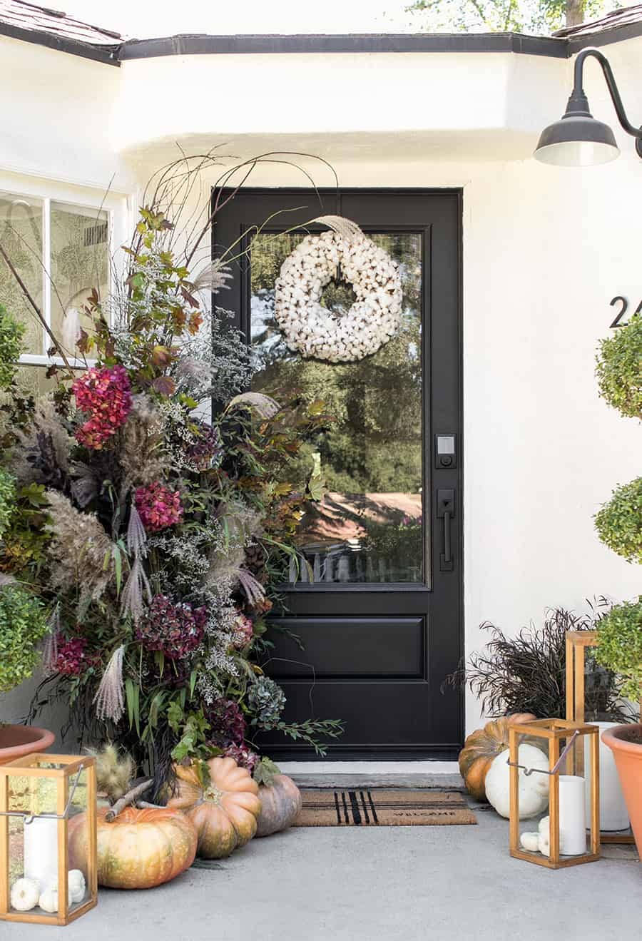 Fall front porch with black door and white wreath with flower arrangements and pumpkins.