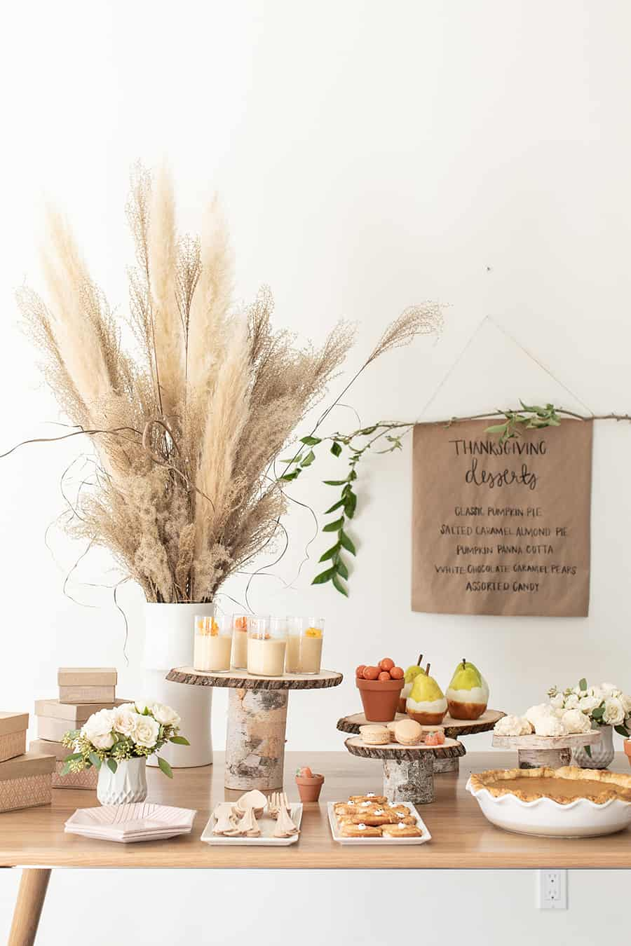 Thanksgiving dessert table with birchwood cake stands and flowers in a white vase.