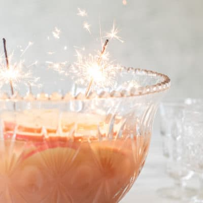 A punch bowl with Spiced Apple Sparkling Holiday Punch recipe and sparklers