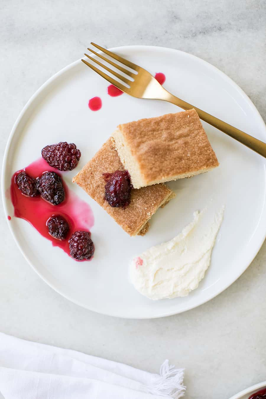 Brown sugar cake on a white plate with blackberries.