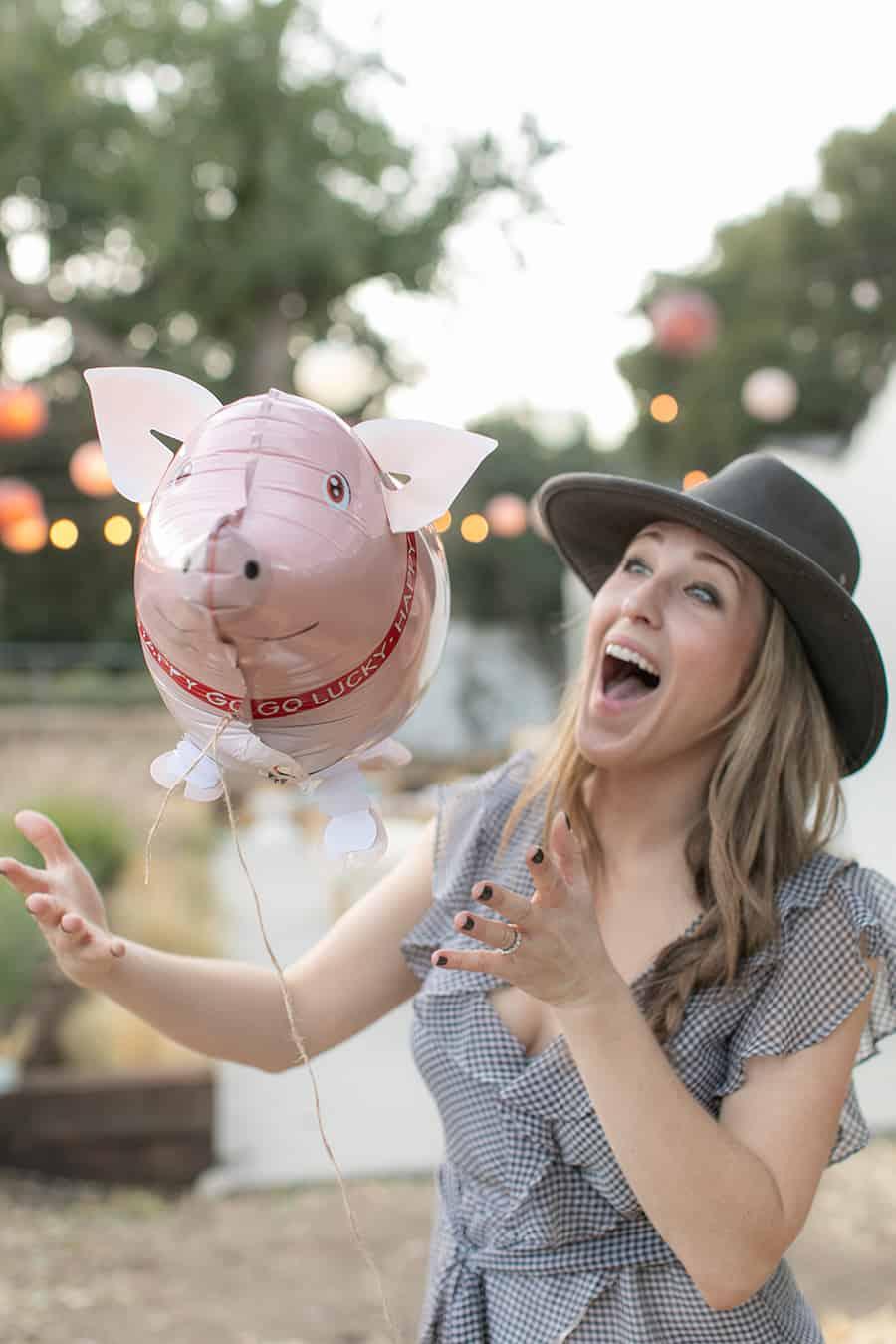 Eden Passante holding pig balloon